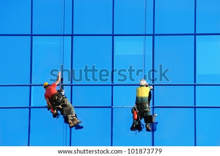 Two wahsers wash facade windows of modern skyscraper