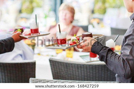Two waiter carrying a plate with different sweet dessert dish on a wedding - stock photo