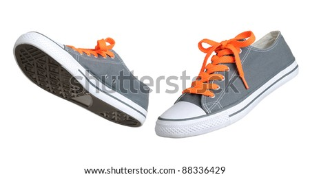 Two walking grey sneakers isolated on white background - stock photo
