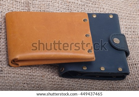Two wallets. Black and Brown leather wallet with money inside, excellent quality leather, zipper on the buttons, handmade. Background on rough linen fabric. - stock photo