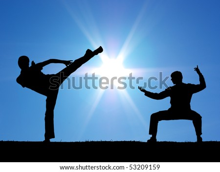 Two warrior silhouettes on the sun background. - stock photo