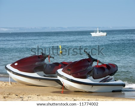 Two water jet skies parked on the beach