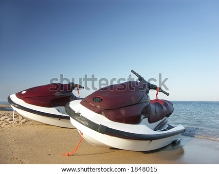 Two water jet skies parked on the beach - stock photo