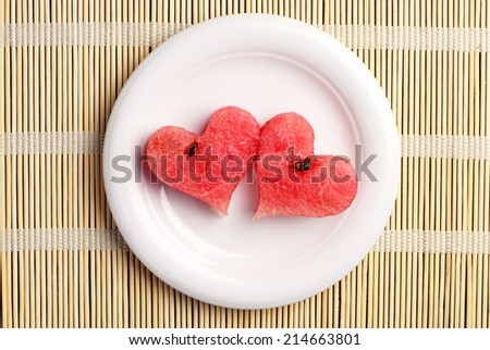 Two watermelon slices in the shape of hearts on a bamboo tablecloth. Top view
