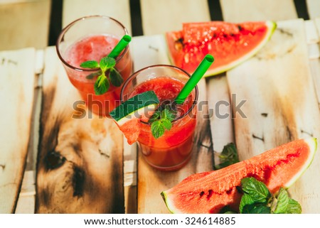 two watermelon smoothie  and fresh on a light wood background. selective focus to mint - stock photo