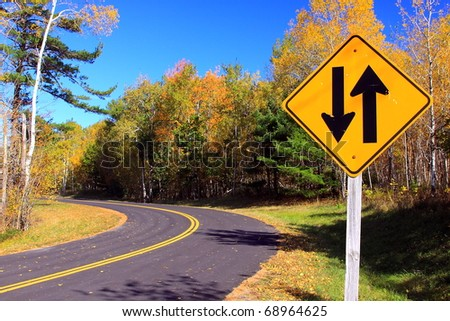 Two way sign with the road in autumn - stock photo