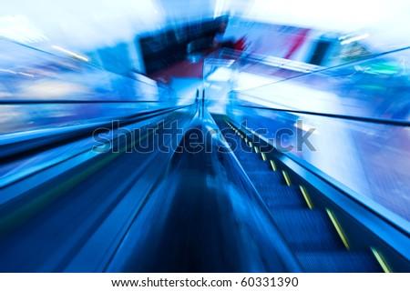 Two ways escalator in blue tone.  ( motion blur) - stock photo