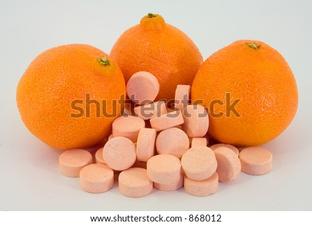 Two ways of getting vitamin c, fruits or pills. - stock photo