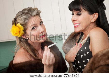Two wealthy Caucasian women smoking marijuana in the kitchen - stock photo