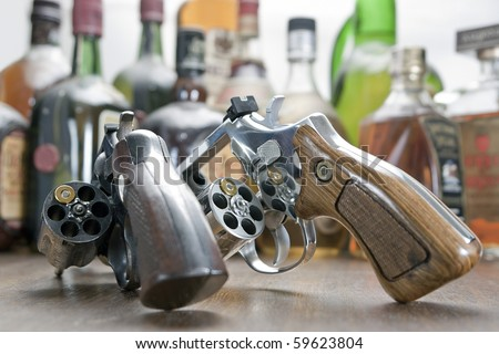 Two weapons with only one bullet each. At the bottom a few bottles of whiskey. Concept of challenge and test of courage. - stock photo
