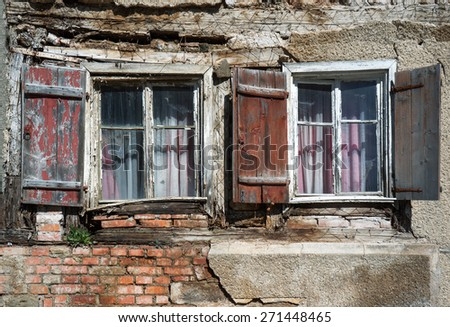 Two weathered windows with shutters and curtains in the ruin of an abandoned house  - stock photo