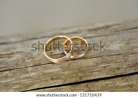 two wedding golden on wooden surface - stock photo