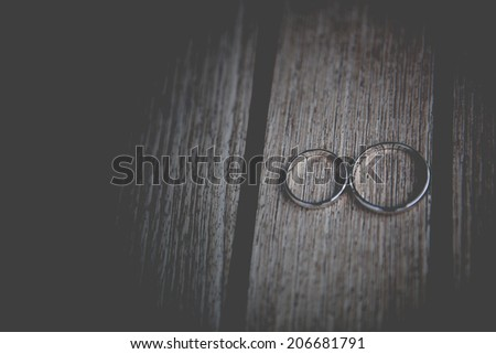 two wedding golden rings on wooden surface - stock photo