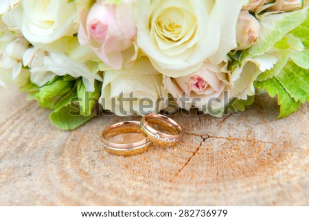 two wedding ring on wooden ground with wedding bouquet - stock photo