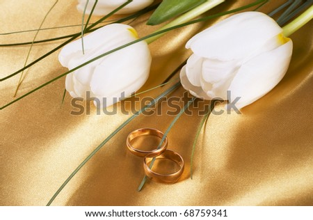 Two wedding rings and flowers tulips lie on bed silk