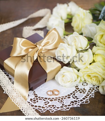 two wedding rings and white roses - stock photo