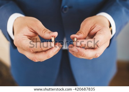 Two wedding rings in a hand of the groom - stock photo