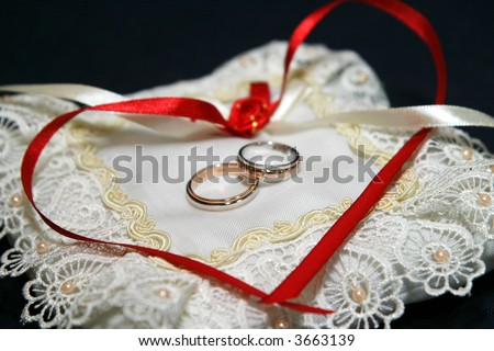 Two wedding rings lay on a pillow the decorated rose and color tapes in the form of heart - stock photo