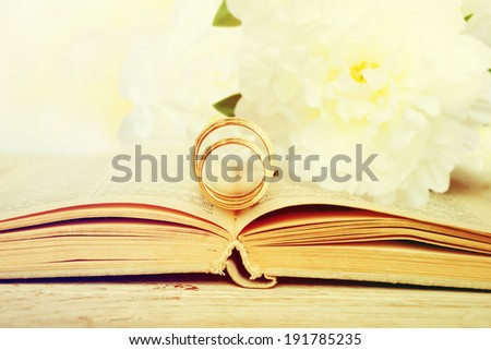 Two wedding rings on a bible page.  - stock photo