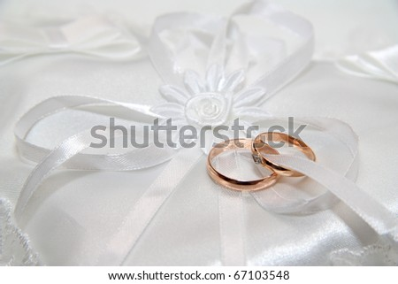 Two wedding rings, on a white small pillow. - stock photo