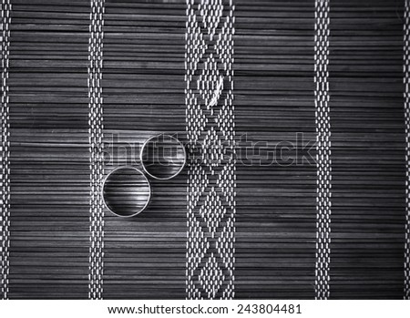 Two wedding rings on bamboo mat. Black and white photo. - stock photo