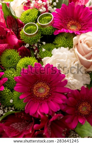 Two wedding rings on the scented and delicate flowers of a bridal colorful bouquet with purple daisies, white carnations and pale pink roses. - stock photo