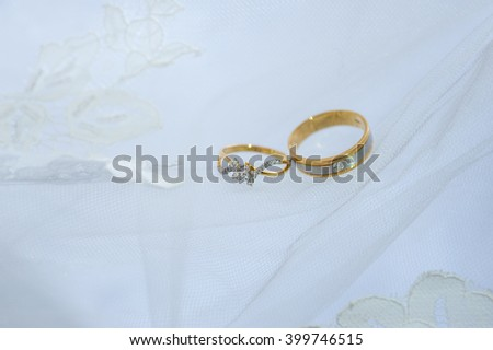 Two wedding rings on white bride dress in the background. place for text (copy space). Can be used in invitation, advertisement, as nice romantic and blurred background. select focus in soft light - stock photo