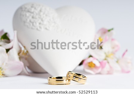 two wedding rings with flowers and a heart in the background - stock photo