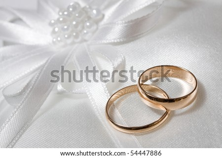 Two wedding rings with white flower in the background. - stock photo