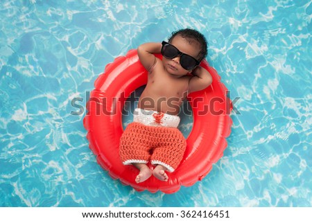 Two week old newborn baby boy sleeping on a tiny inflatable swim ring. He is wearing crocheted board shorts and black sunglasses. - stock photo