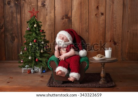 Two week old, newborn, baby boy wearing a crocheted Santa suit with beard. He's sleeping on an armchair. Shot in the studio with props, such as a Christmas tree, glass of milk and crocheted cookies.  - stock photo