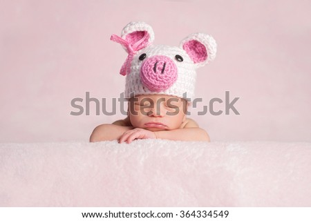 Two week old newborn baby girl wearing a pink, crocheted, piglet costume. She is sleeping on a soft, fuzzy, pink blanket. - stock photo