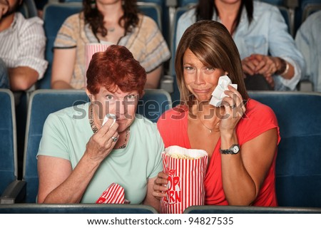 Two weeping women in the audience with tissue paper - stock photo