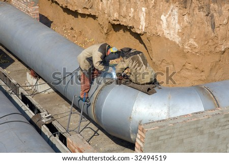Two welders are making the trunk pipeline. - stock photo