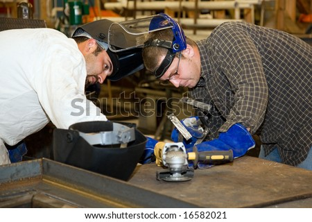 Two welders working together on a difficult metal work project.  Authentic and accurate content depiction in compliance with industry code and safety standards. - stock photo