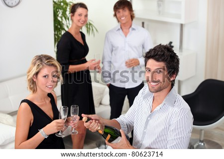 two well dressed couples drinking sparkling wine in a living room - stock photo
