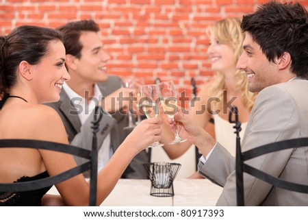 two well dressed couples toasting at the restaurant - stock photo