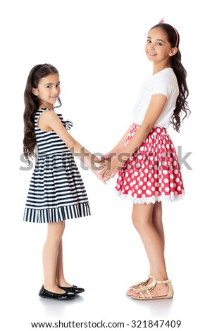 two well-dressed girls sisters Oriental appearance are opposite each other and hold hands.-Isolated on white background - stock photo
