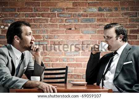 Two well dressed men in suits have coffee together, dramatic lighting - stock photo