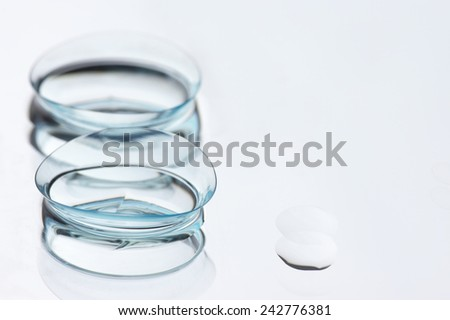 Two wet soft contact lenses with reflection close-up on light background with copy space. Shallow DOF. - stock photo