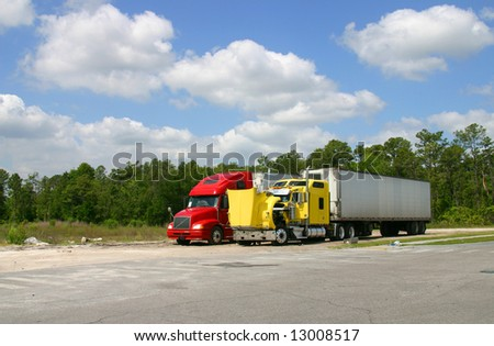 Two 18-wheeled trucks, one yellow, one red, stopped for maintenance. Yellow truck's hood is open. - stock photo