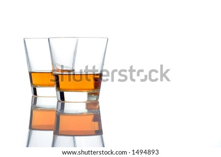 Two whiskey glasses against white background - stock photo
