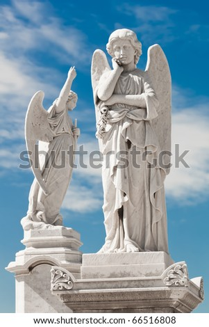Two white angels with a beautiful sky background - stock photo