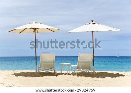 Two White Beach Chairs and Umbrellas