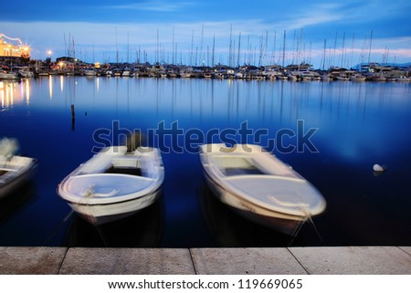 Two white boats floating on water at blue sky - stock photo
