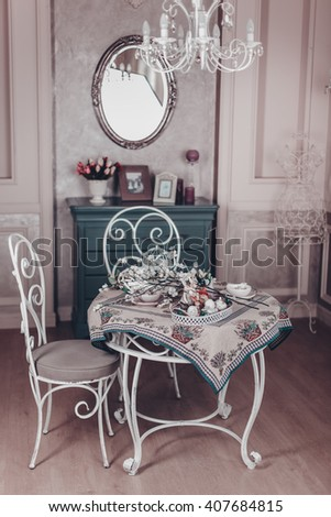 two white chair and a table covered with a tablecloth, Provence style, retro, vintage interior, Paris France, still life on the table, flowers purple and white, wrought-iron cage, braided wreath - stock photo