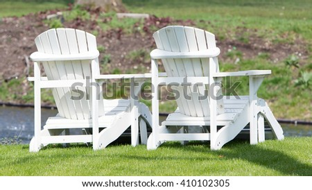 Two white chairs at the waterfront, dutch garden