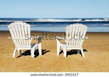 Two white chairs on the beach - stock photo
