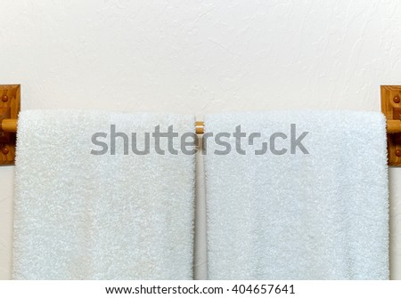 Two white cotton terry cloth towels hanging on an off white wall from wooden rack.