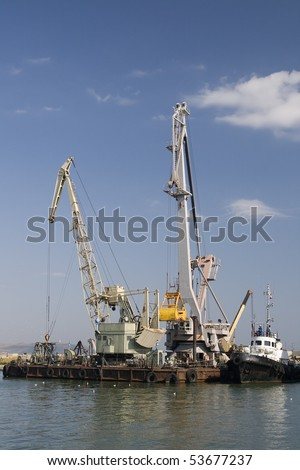 Two white cranes in a harbor on water's edge